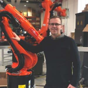 Billede af MIchael Friis med KUKA robotter i baggrunden.